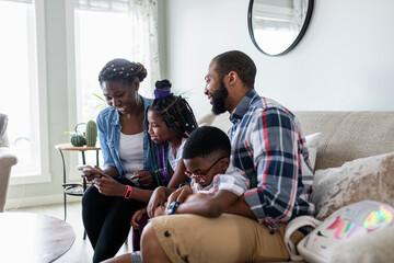 Happy family using smart phone on living room sofa
