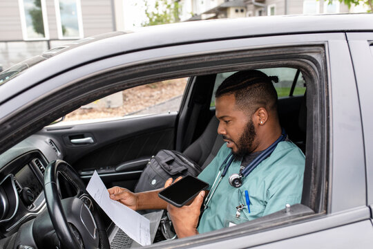 Male home caregiver recording audio notes with smart phone in car