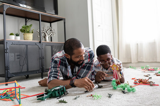 Father and son playing with toys on bedroom floor