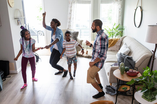 Happy family enjoying dance party in living room