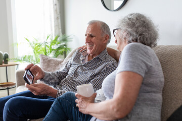 Happy senior couple using smart phone on sofa