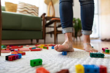 Mother stepping on plastic block toys on living room floor