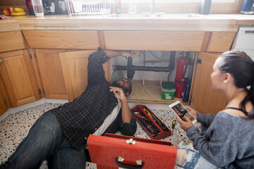Couple watching DIY video on digital tablet fixing kitchen pipes