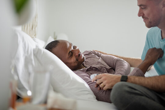 Affectionate gay man caring for sick husband resting in bed