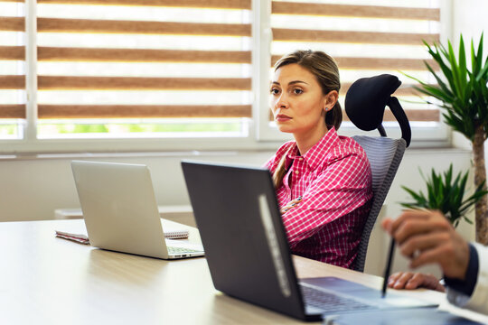 Young caucasian woman entrepreneur or manager sitting at the office at company having a meeting - Female CEO working on business day in front of laptop computer side view