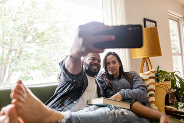 Happy couple taking selfie with camera phone on sofa