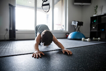 Boy doing stretch exercise in home gym