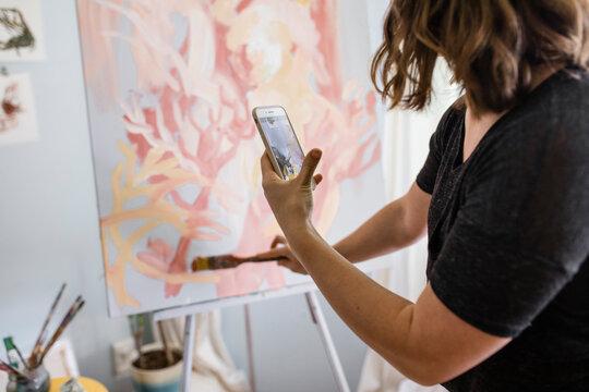 Artist videoing her brush strokes on painting