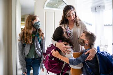 Mother hugging children wearing face masks