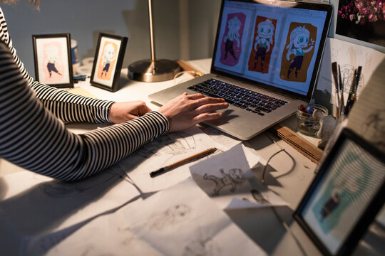Young female artist looking at her caricatures on laptop
