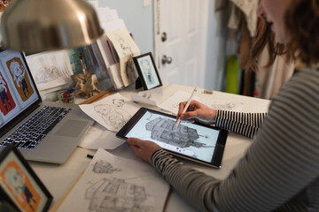 Young female artist drawing with digital tablet