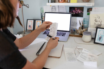 Artist checking her receipts using laptop