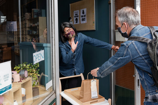 Cafe owner wearing face mask serving man at doorway