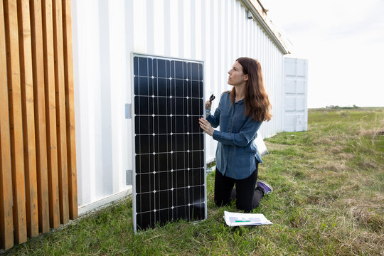Woman fitting solar panels to container home