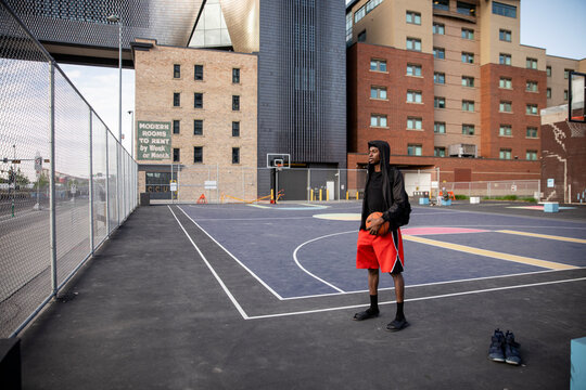 Young man with basketball on urban court