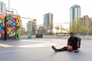 Portrait confident young man on urban basketball court with mural