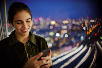 Smiling businesswoman with smart phone working late at office window