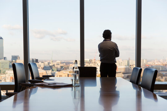 Thoughtful businessman looking out urban conference room window