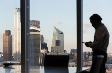 Businessman using smart phone at highrise office window, London, UK