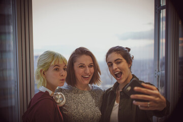 Happy businesswomen taking selfie at office window