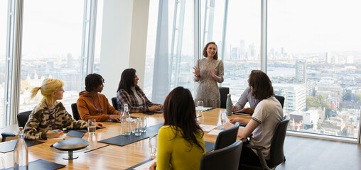 Businesswoman leading conference room meeting in highrise office