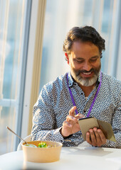 Smiling businessman using smart phone at lunch