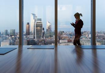 Businesswoman using smart phone at highrise office window, London, UK