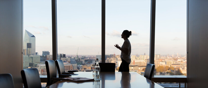 Businesswoman preparing for meeting in highrise conference room