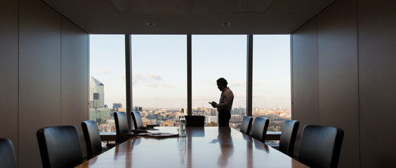 Businessman using smart phone at highrise conference room window