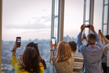 Business people with camera phones photographing city