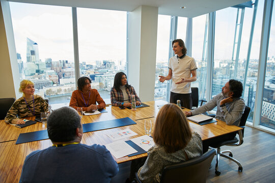 Businessman leading conference room meeting in highrise office