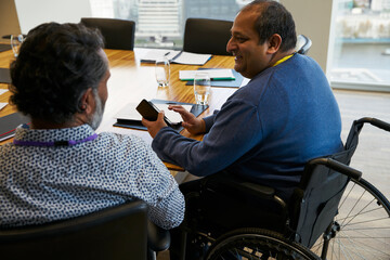 Businessman in wheelchair talking with colleague in meeting
