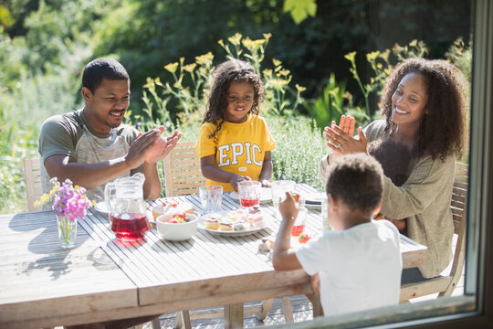 Happy family clapping and eating at sunny summer patio table
