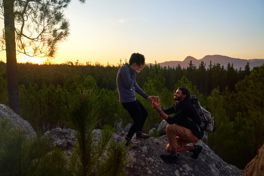 Young man with engagement ring proposing to woman on rock at sunset