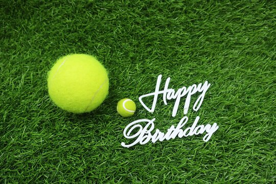 Tennis ball with Happy word for Birthday Greeting is on green grass