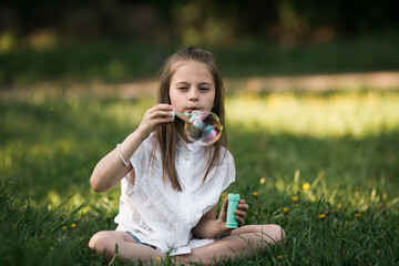 Little girl blowing bubbles sitting on the grass in the park.