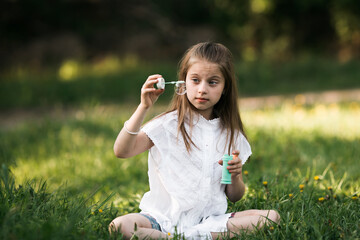Ten-year-old girl blowing bubbles sitting on the grass in the park.