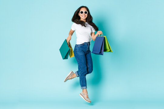 Fashion, beauty and lifestyle concept. Carefree attractive and happy asian girl in sunglasses, jumping from happiness after shopping, holding bags with clothes, standing light blue background