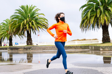 Athletic woman running with face mask down the street