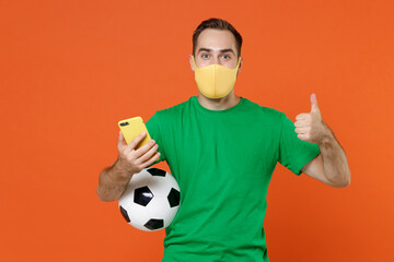 Man football fan in green t-shirt face mask to safe from coronavirus covid-19 support favorite team...