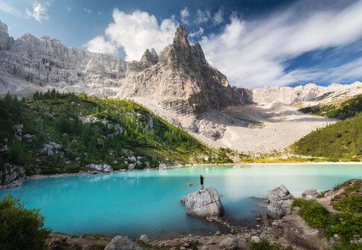 Amazing view of Sorapis lake (Lago di Sorapis) with man on the rock looking on the mountain Dolomites