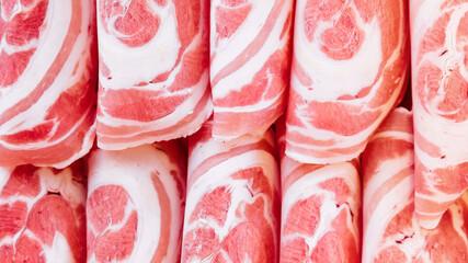 Close-up Premium Rare Slices Kurobuta (Black Pig) pork with high-marbled texture on circle wooden plate served for Sukiyaki and Shabu.