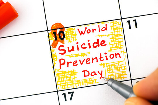 Woman fingers with pen writing reminder World Suicide Prevention Day in calendar.