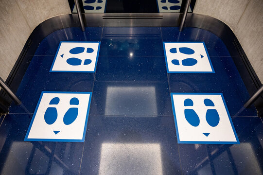Blue glossy floor of passenger lift or elevator with standing marker for social distancing to avoid spreading coronavirus. Foot symbol position for preventing COVID-19 pandemic in public building.