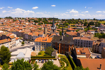 View from drone of Craponne-sur-Arzon summer cityscape with black Gothic steeple of parish church...