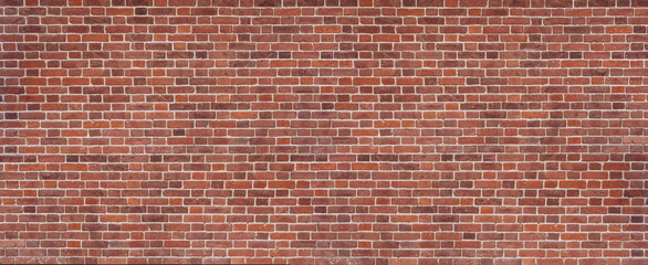 Panoramic background of wide old red and brown brick wall texture. Home or office design backdrop.