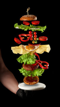 flying cheeseburger ingredients: meat cutlet, sesame bun, cheese, fried egg, tomato and green lettuce on a black background