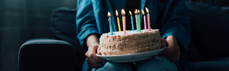 panoramic crop of woman holding birthday cake with candles
