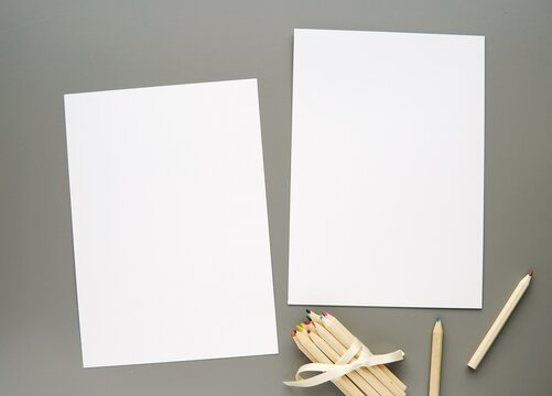 Two white empty paper sheets, wooden pencils on grey background, coloring page, planner mockup, back to school concept.
