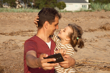 little happy daughter hugs daddy selfie on beach on sunny day